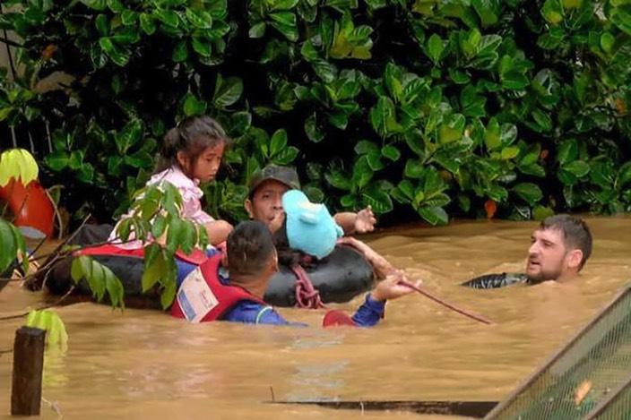 Thomas Kellenberger (rechts) hilft während des Taifuns bei der Evakuation von Kindern mit.