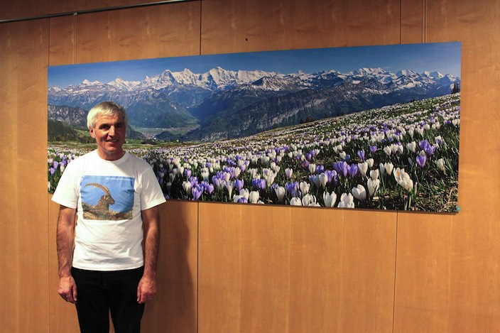 Hobbyfotograf Fritz Bieri vor einem Panoramabild seiner Bergheimat.