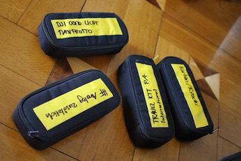 Das Zubehör für die Kameraausrüstung ist auf verschiedene, beschriftete Etuis verteilt.