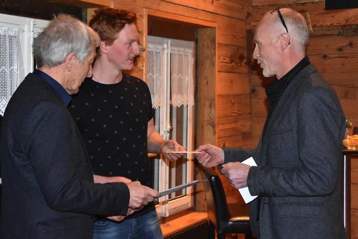 Christian Jossi (rechts) überreicht Nicola Lubasch (Mitte) ein Geschenk. Vom Gemeindepräsidenten erhält der Bronzemedaillengewinner eine Urkunde.
