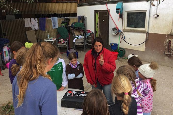 Die Voltis aufmerksam bei der Sache: Lagerleiterin und Trainerin Irène Zumkehr erklärt, was alles in einen Erste-Hilfe-Koffer für Pferde gehört.