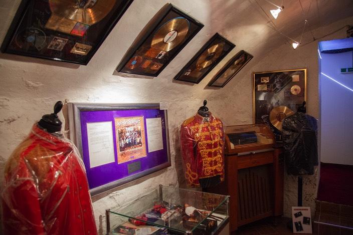 Violett eingebettet hängen die Verträge und das Plattencover von «We are the World» an der Wand.